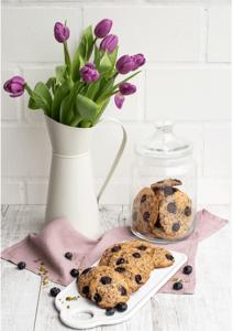 Cookies mit Keksglas und Vase mit Tulpen