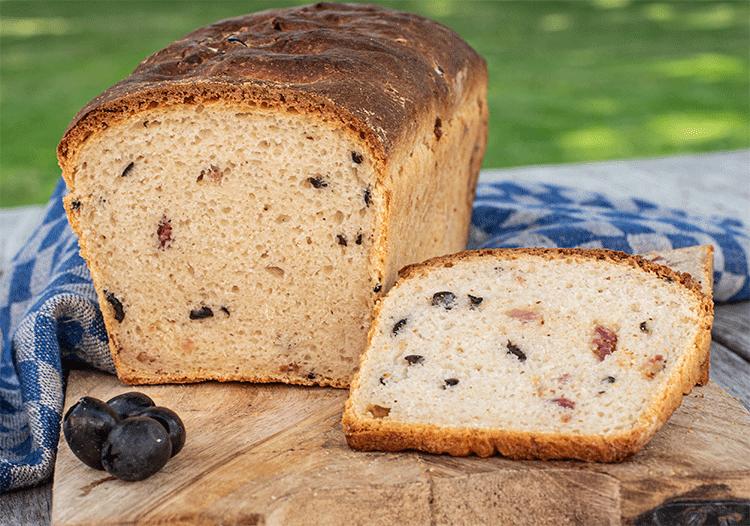 Anschnitt saftiges Brot mit Oliven, Käse und Speck